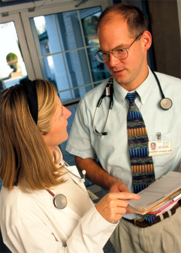 Two physicians with stethoscopes speaking to one another